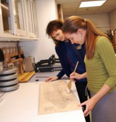NLM conservators lean over a old map