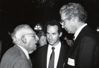 Three men in a conversational cluster