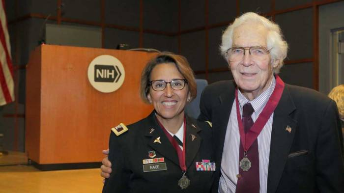 Dr. Lindberg stands with his arm around Colonel Nace. Both are wearing the Ordre of Military Medical Merit medallion.