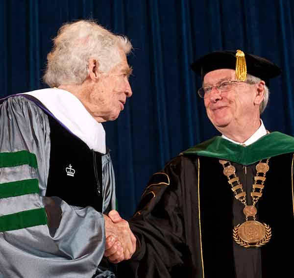 Dr. Lindberg and Dr. Rice, in full academic regalia, shake hands on stage after the honorary degree is conferred.