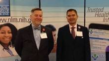 Dale Prince and Tony Nguyen stand in front of NLM banners at their exhibit booth.