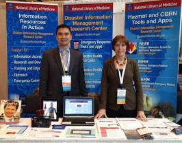 Tony Nguyen and Elizabeth Norton stand behind their exhibit table on which are displayed a variety of print resources on disaster information management.