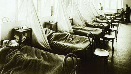 Men lie in cots positioned close together, with rudimentary privacy provided by sheets hung between them..