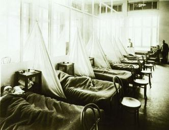 Men lie in cots positioned close together, with rudimentary privacy provided by sheets hung between them.