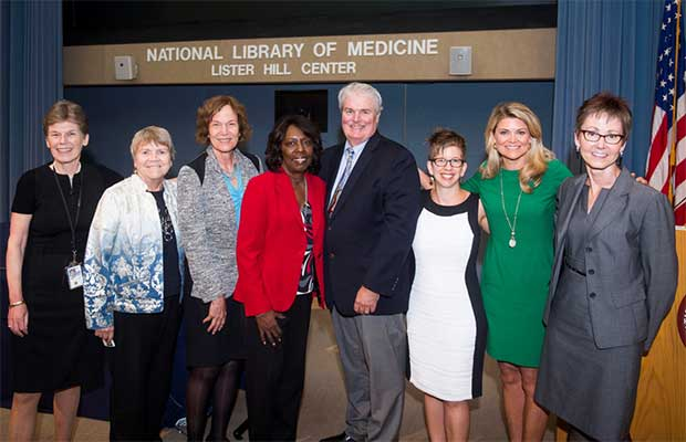 Opening events participants stand together in front of the stage at the NLM Lister Hill Center Auditorium.