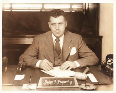 John Fogarty sits behind his desk, pen in hand.