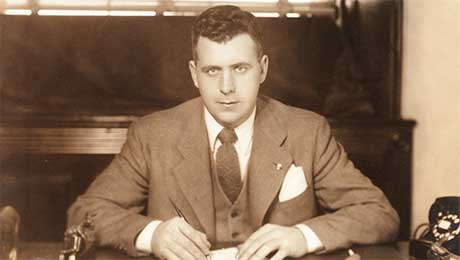 John Fogarty sits at his desk, pen in hand.