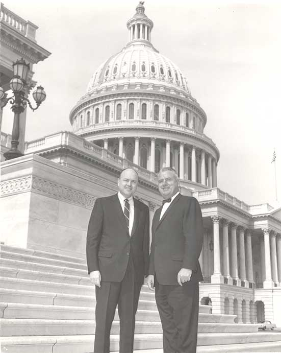 Fogarty and Laird stand on the U.S. Capitol steps, the dome of the Capitol visible behind them.