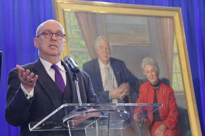 Glen Campbell stands at the podium, the portrait of Dr. and Mrs. Lindberg visible behind him.