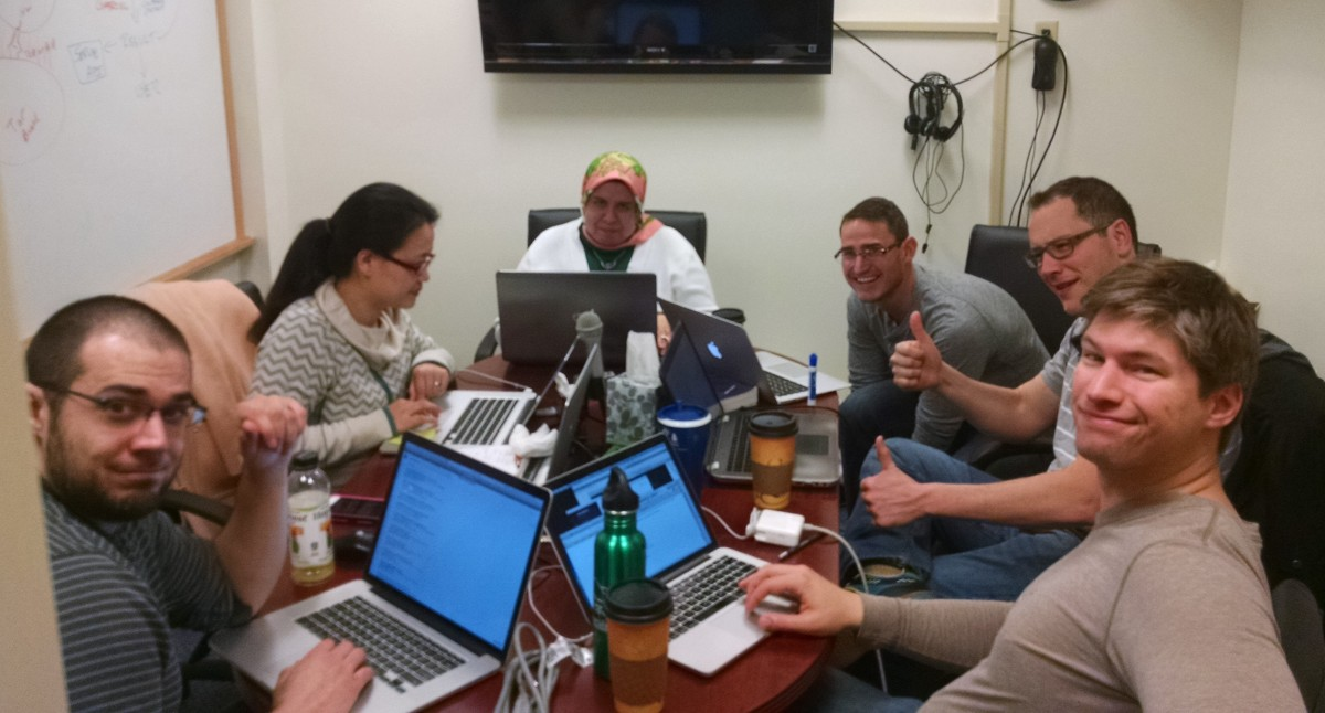FFour men and two women work at a table, laptops open.
