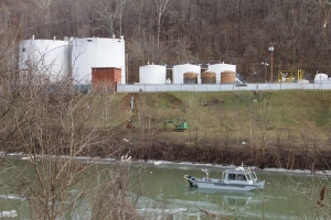 Boat on the river, chemical tanks on the bank above