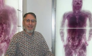 Dr. Ackerman stands in front of plexiglass models created using the visible human data