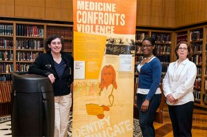 Exhibition team members stand with a banner from the Confronting Violence exhibition.