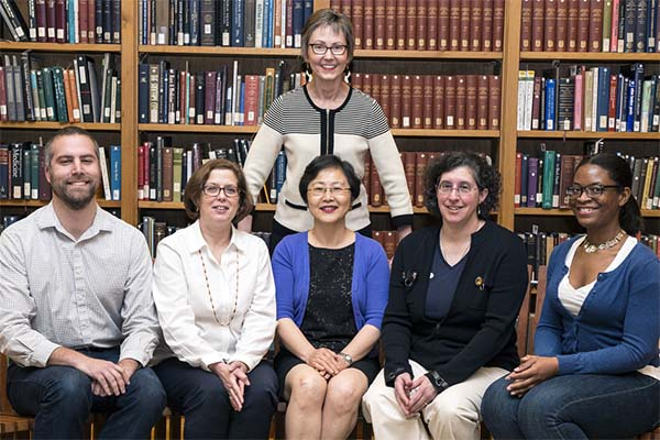 Patricia Tuohy stands behind five members of the exhibition team seated in the History of Medicine Reading Room.
