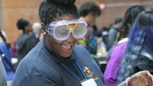 A high school girl wearing safety goggles smiles broadly.