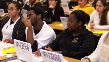 Students in a classroom listen attentively to a presentation.