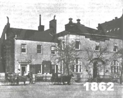 Black and white photo of a brick building, in front of which stands two horse-drawn carriages
