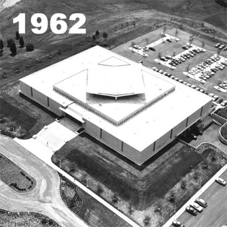 The library building sits on cleared land with minimal foliage. Parking lots are visible along the perimeter.