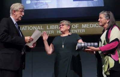 Dr. Collins reads from a piece of paper, while Dr. Brennan stands with her right hand raised, her left hand on a large book held by her sister.