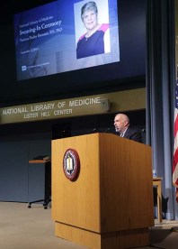 A man stands behind a podium, with a presentation slide visible behind him