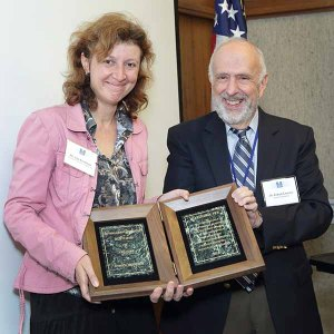 A smiling woman and man together hold a wood and marble award.