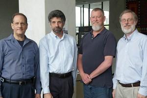 Four men stand shoulder to shoulder
