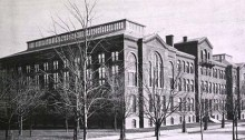 Large, imposing brick building in front of which stand bare trees