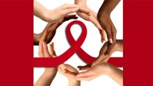 hands of various colors form a circle around a red ribbon