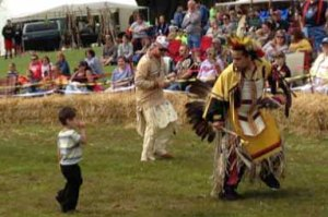 Child watches a young dancer in Native American garb