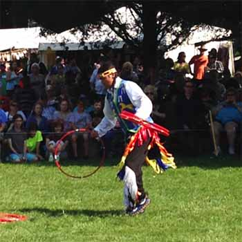 Young Native American man in traditional garb dances with red hoops