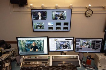Four large monitors offer different views of the space chat featuring Collins and Rubins