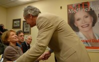 Senator Harkin leans over a seated Mary Tyler Moore and shakes her hand.