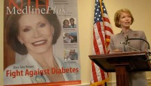 Mary Tyler Moore stands at a podium. Visible to her right is a blow-up of the magazine cover featuring Moore.