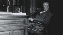 A man is seated at desk, leaning back in armchair (view from the side)
