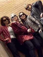 Four women wearing dark sunglasses strike intimidating poses