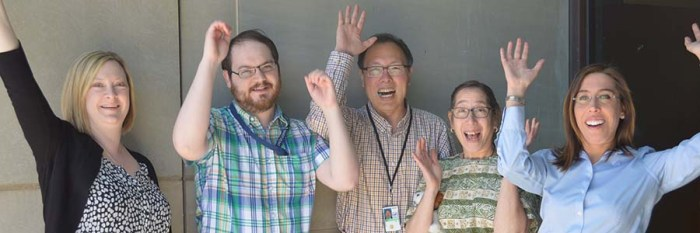 The DOCLINE® team raise their hands in celebration and smile.