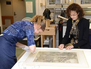 Two women give close attention to a print of a human skeleton