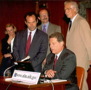 Gore sits in front of a laptop while the others stand behind him