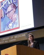 Dr. Shelly McKellar speaks from the podium with a picture behind her of Dr. DeBakey on the cover of Time magazine.