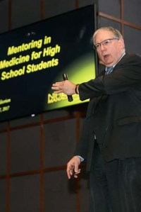 Dr. Tabak gestures while speaking from the stage