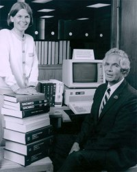 Humphreys stands behind a short stack of books while Lindberg sits in front of a computer
