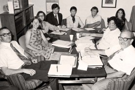 Nine people sitting around a conference table