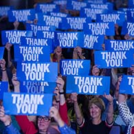 """Audience members hold signs reading """"thank you"""" above their heads"""