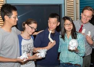 Group shot of five people holding medical models