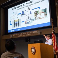 Dr. Brennan gestures from behind a podium toward the projected slide behind her