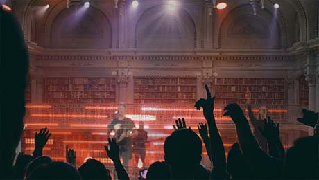 A crowd in silhouette watch a rock band perform against the backdrop of a library