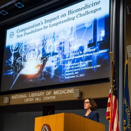 Dr. Córdova, PhD, speaks from behind a podium, her presentation visible behind her