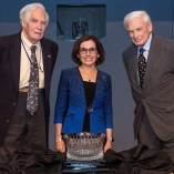 Two men and a woman smile, a crystal bowl on a table in front of them
