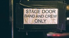 "Sign taped to stage door reads, ""Band and crew only."""