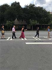 four women and a man walking across a road